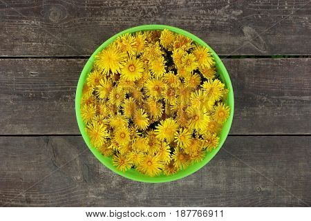 Green Basket With Yellow Flowers Of Dandelions On The Brown Wooden Background.