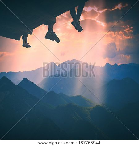 Hikers sit on a wooden flooring above the mountain valley and enjoy golden sunset. Instagram stylisation.