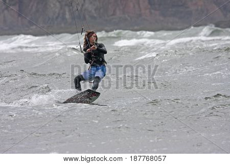 kitesurfer riding his board on the sea