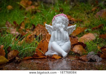 Tiny angel figure next to a child grave in cemetery