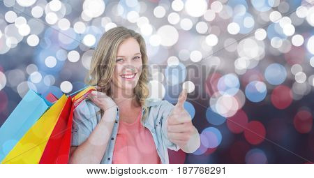 Digital composite of Woman holding shopping bags while gesturing thumbs up over bokeh
