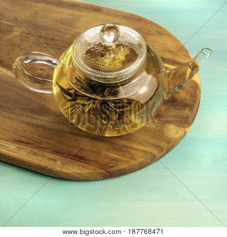 A square photo of a teapot with a tea flower in it, with a place for text