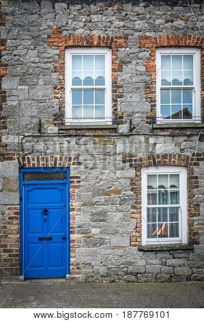 Typical blue front door and windows in an old home in Limerick, Ireland
