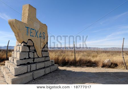 Traditional stone-made sign welcoming to the state of Texas on a rural road