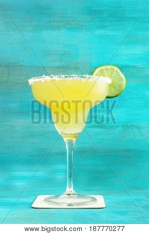 Lemon Margarita cocktail with a wedge of lime on a vibrant turquoise background with copy space