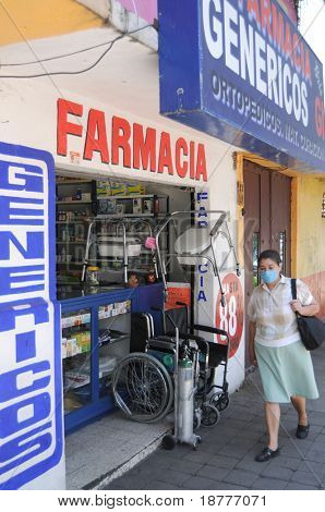 MEXICO CITY - APRIL 28: A woman wearing a face mask walks past a pharmacy on April 28, 2009 in Mexico City. Concern over the Swine Flu spreads worldwide.