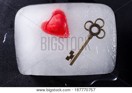 Heart and key frozen in a block of ice