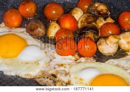 Muschrooms Tomatoes And Egg Cooking In A Frying Pan