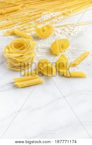Various types of pasta on a white marble table with flour and a place for text