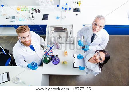 Top Up Of Lab Team Of Three Researchers Working With Reactants And Looking Up, Professor Is Old And