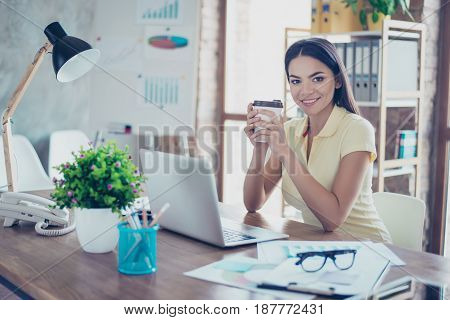 Smiling Young Mulatto Girl Is Drinking Coffee At The Break In Office, Wearing Casual Clothes