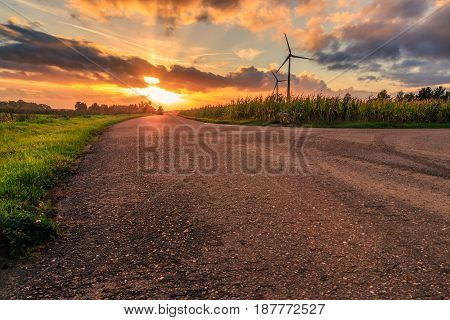 Rural scene cloudy sunset with an empty road corn fields and wind turbines. Diest Flanders Belgium Europe