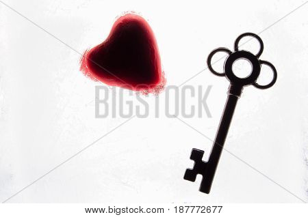 Silhouette of a red heart and key on white background