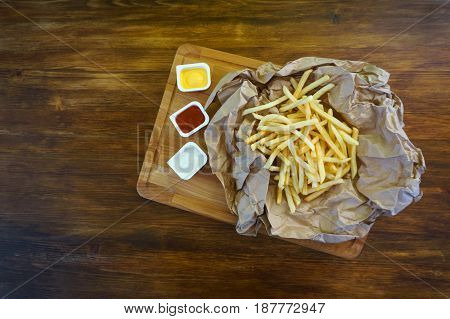 Fresh fry potatoes on wooden board with sauces, top view photo
