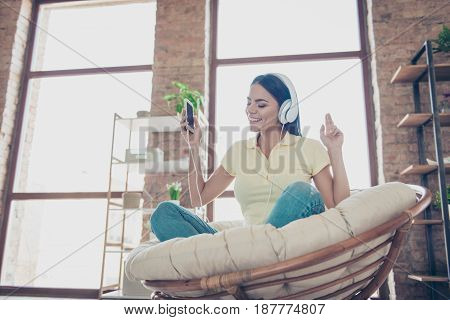 Portrait Of Beautiful Happy Latin Mulatto Girl Sitting In Stylish Armchair At Home With Phone And Li