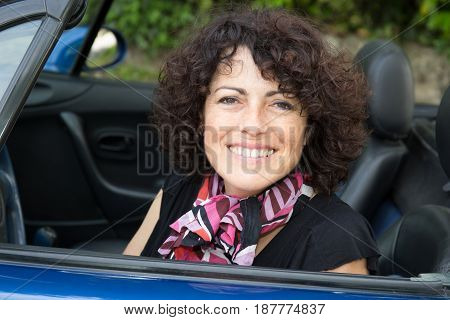 Forties Woman With A Pink Scarf Sitting In A Convertible Car