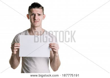 A Young Handsome Guy With A Blank Sheet Of Paper, Looking At The Frame With Perplexity. Place For Si