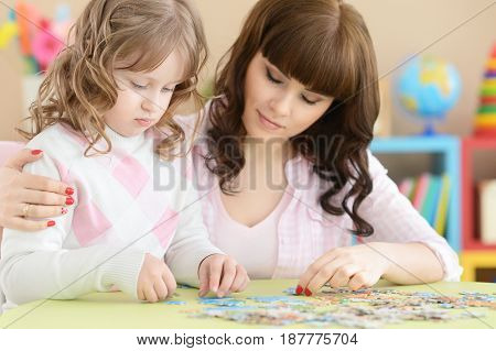 Mother and daughter are playing at the table