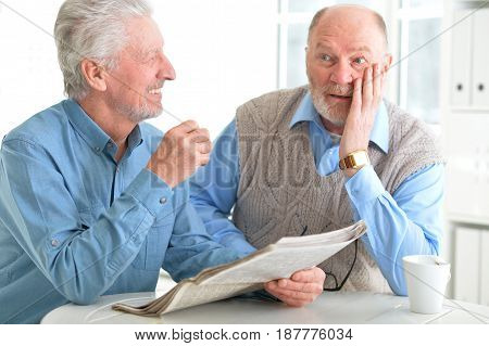 Old men reading a newspaper at a table