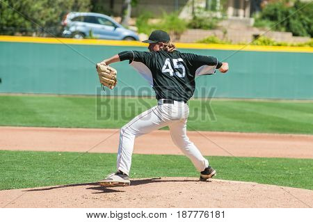 Mens' baseball pitcher winding up to throw the curveball.