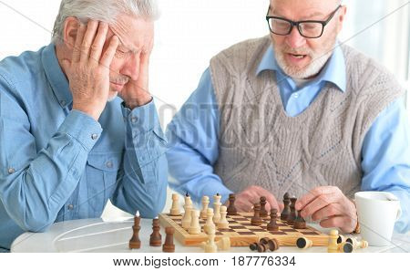 Beautiful old men play chess at the table