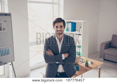 Success Concept. Excited Business Man Is Standing In A Suit With Crossed Hands And Smiles. His Offic