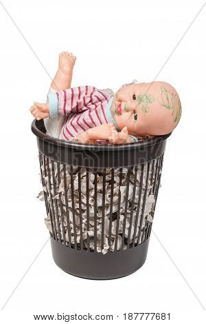 Old painted doll in a garbage can with toilet paper, isolated on a white background