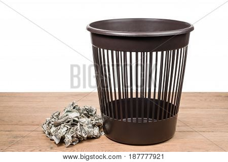 Pile of crumpled dollars lies on a wooden surface next to a trash can on a white background