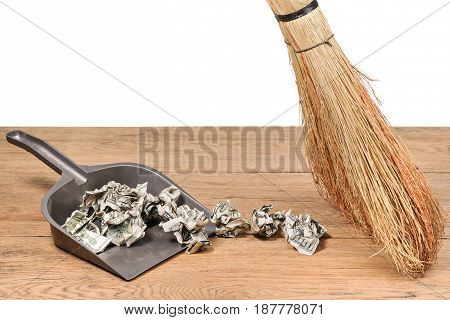 Broom sweep crumpled dollars in a dustbin on wooden table, isolated on a white background