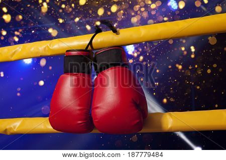 Pair of red boxing gloves hangs off the boxing ring