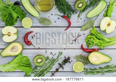 Green fresh vegetables and spices on a white wooden table. Top view. Place for text