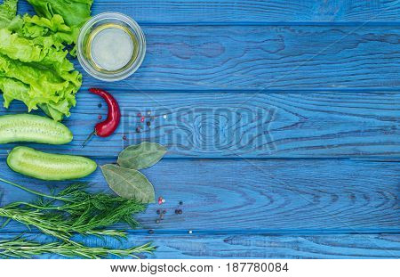 Green fresh vegetables and spices on a blue wooden table. Top view. Place for text