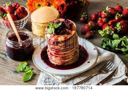 Stack of homemade american pancakes served with jam and strawberries on wooden background.