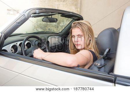 a blonde girl in a convertible car
