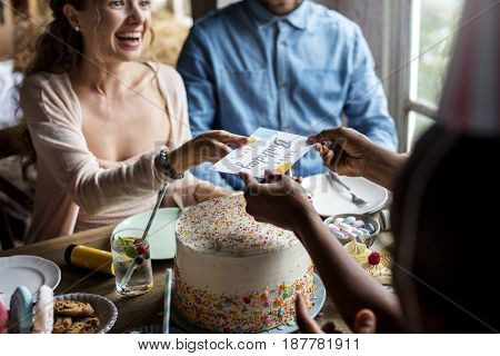 People celebrate birthday party with cake and card