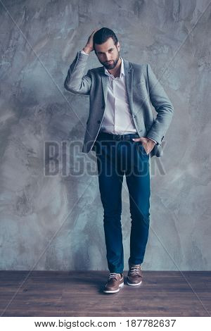 Full Length Portrait Of Classy Young Bearded Business Man, Standing On Gray Concrete Background. He