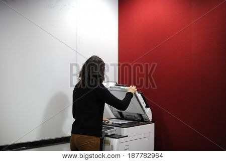 Woman using machine to copy document
