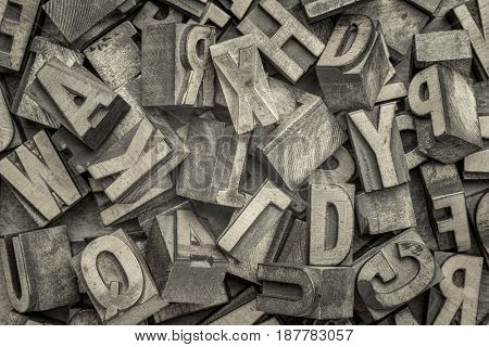 alphabet abstract - background of random letterpress wood type printing blocks, top view, black and white platinum toned image