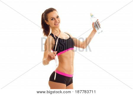 cheerful young athletic girl in tank top and shorts looking at the camera and holding a water bottle isolated on white background