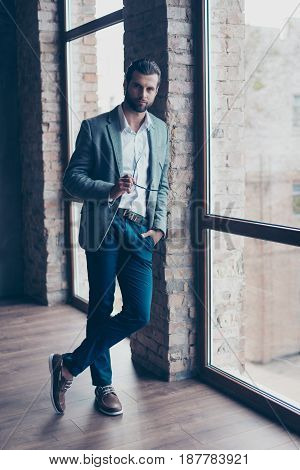 Full Size Of Young Business Man, Who Is Standing Near The Window With Crossed Legs And Looking In Ca
