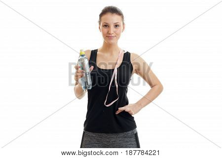 cute young fitness girl in black shirt looks into the camera with the measuring tape and water in hand isolated on white background