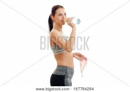 Athletic beautiful slender girl stands sideways in a gray top and drinking mineral water isolated on white background