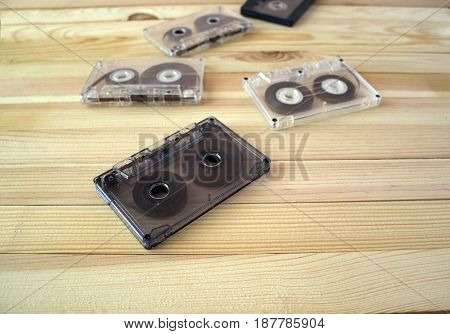 Several audio cassettes lie in a row on a wooden background