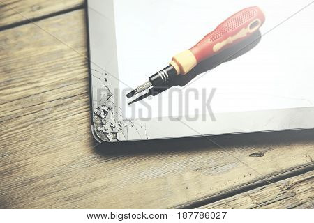 screwdriver on a cracked broken touchscreen tablet