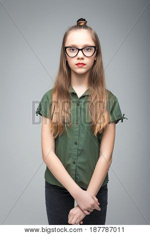 Portrait of young beautiful spectacled girl over gray background. woman dressed in green T-shirt
