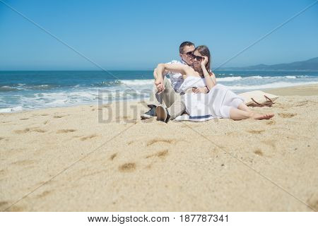 Young romantic couple sitting on the beach, man in sunglasses, woman in white dress, holding hat, talking.