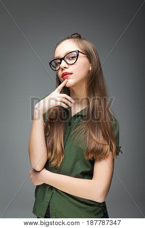 Portrait of young beautiful spectacled girl over gray background. woman dressed in green T-shirt. red lips