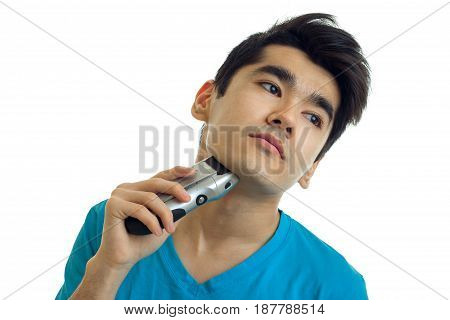Portrait of a young man who is a luxury bending head looks away and shaves machine is isolated on a white background