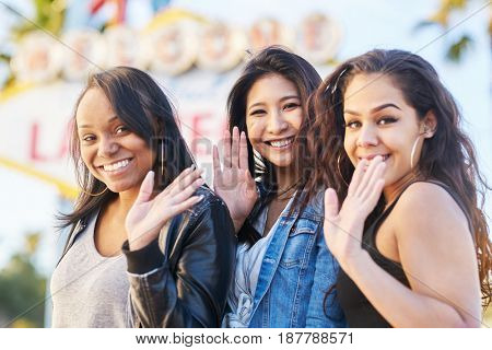 all girl group of friends having at camera in front of welcome to fabulous las vegas sign