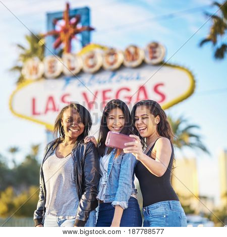 three girls on vacation taking selfie in front of welcome to las vegas sign